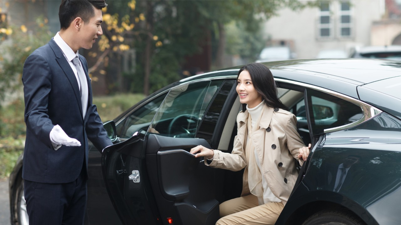 A man opens car door for a woman; Image used for HSBC free airport transfers page.