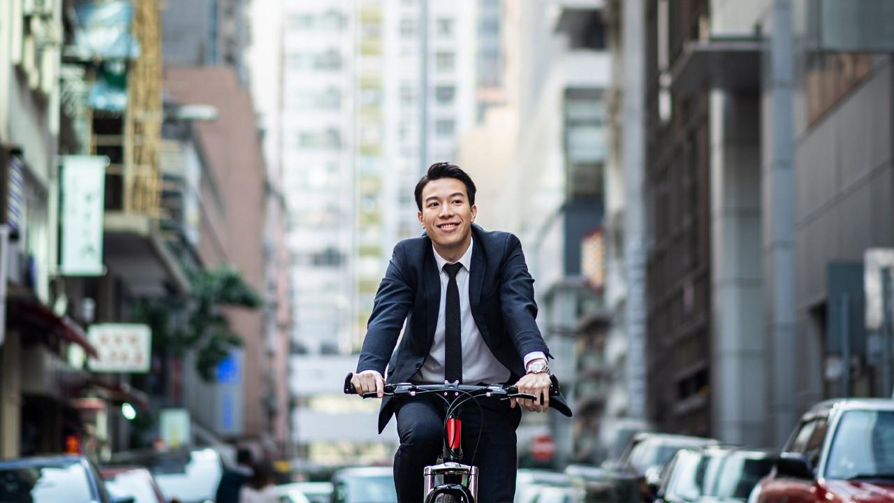 一位男士在鬧市中騎單車;圖片使用於滙豐One能投資講堂頁面。