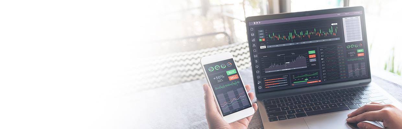 一位男士正在使用電腦和手機投資股票; 圖片使用於滙豐台灣證券分戶帳交割帳戶服務的頁面。