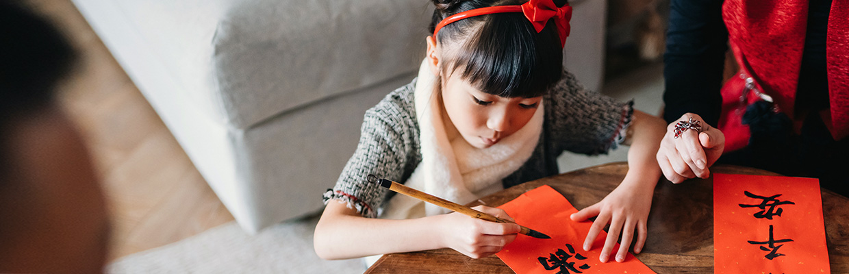 A girl is practicing calligraphy; image used for HSBC mortgages page.