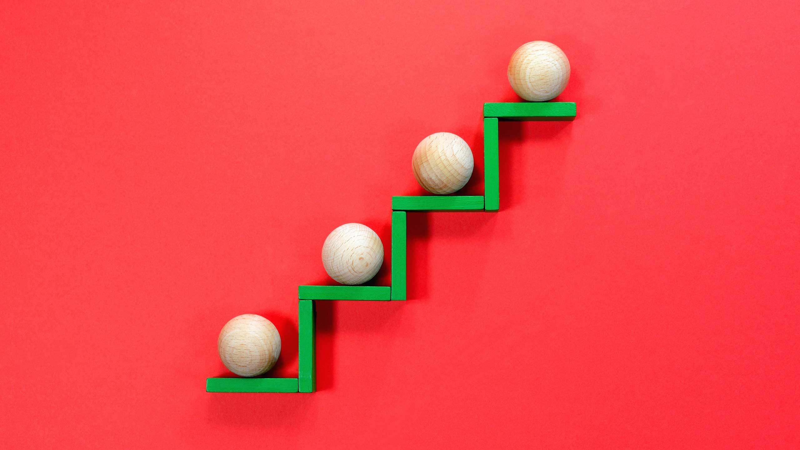 四個木球排列在木架上; 圖片使用於滙豐台灣運籌理財的頁面。