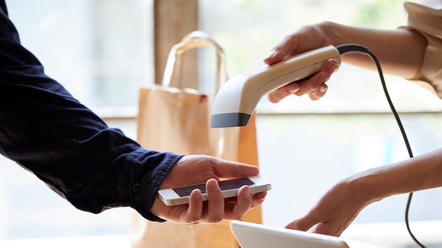 店員為客人掃描手機螢幕上的條碼進行手機支付; 圖片使用於滙豐台灣刷卡消費好禮活動的頁面。