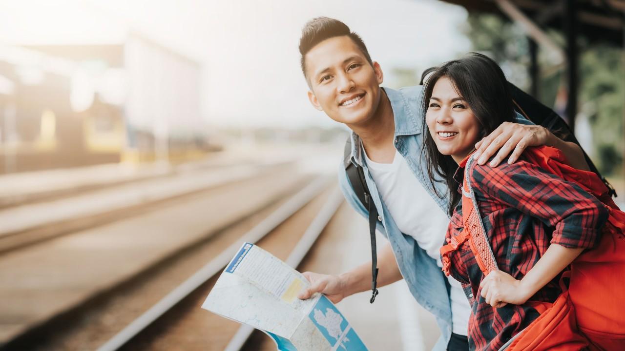 一個男人拿著地圖,擁著身邊女人的肩,一起站在火車軌道旁; 圖片使用於滙豐台灣旅遊平安險及旅遊不便險的頁面。