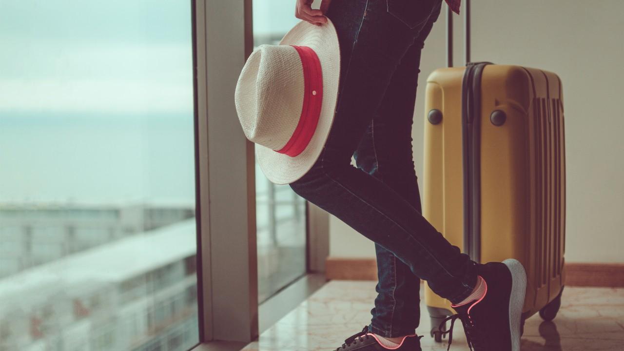 一個人攜著帽子及行李箱站在窗戶旁; 圖片使用於滙豐台灣機場貴賓的頁面。