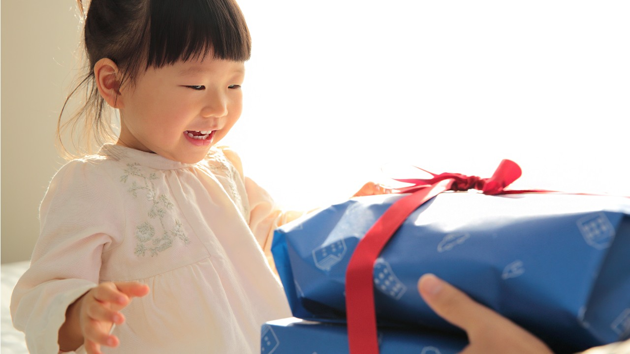 A happy little girl receive her big gift; imaged used for HSBC Taiwan HSBC Cashback Titanium Credit Card page.