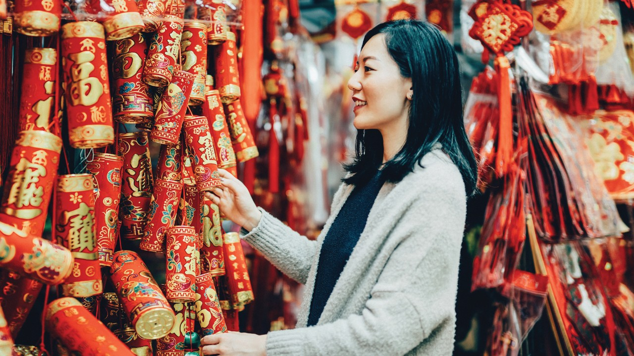 A girl is happliy choosing the Chinese new year coupletes; image used for HSBC Taiwan i-Invest for online trading page.