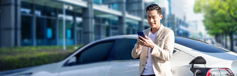 一個男士站在車子旁邊看手機; 圖片使用於滙豐台灣綠動信貸的頁面。