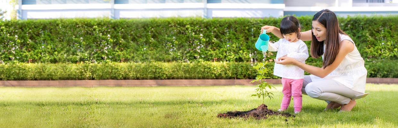 一位小女孩和母親為盆栽澆水;圖片使用於滙豐綠建築優惠房貸頁面。