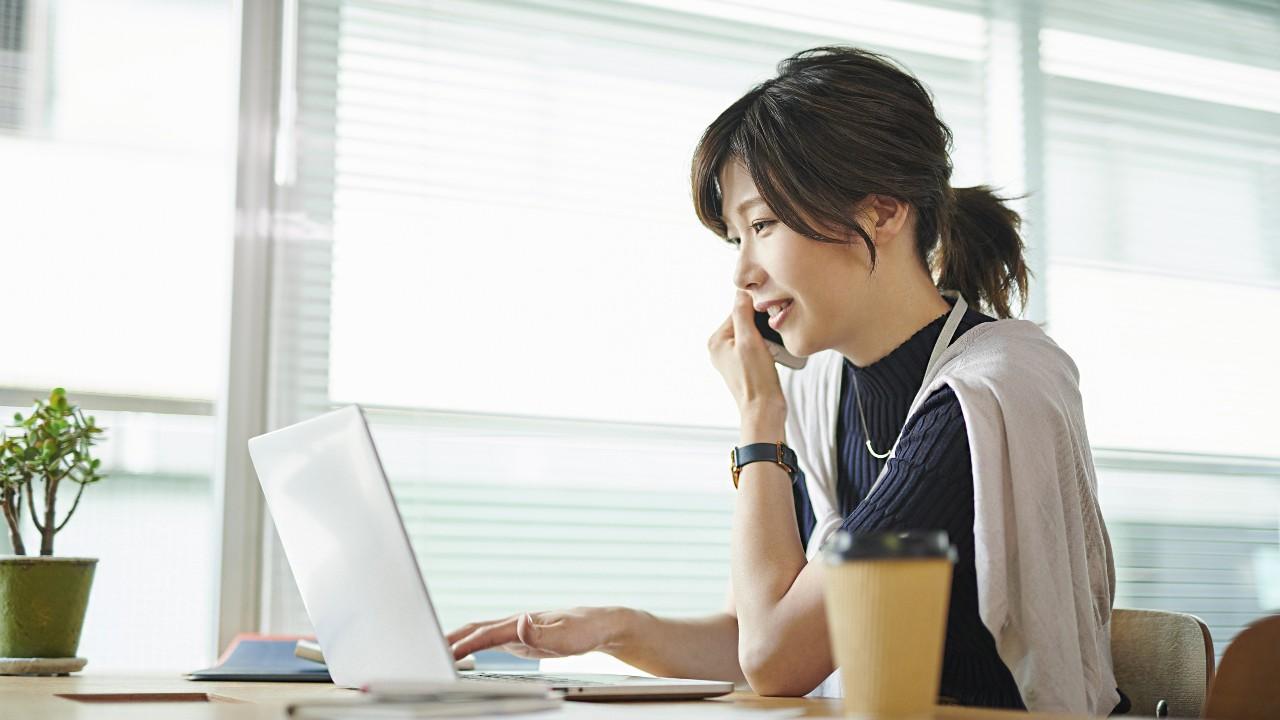 一位女人在電腦前通電話; 圖片使用於滙豐台灣服務據點頁。