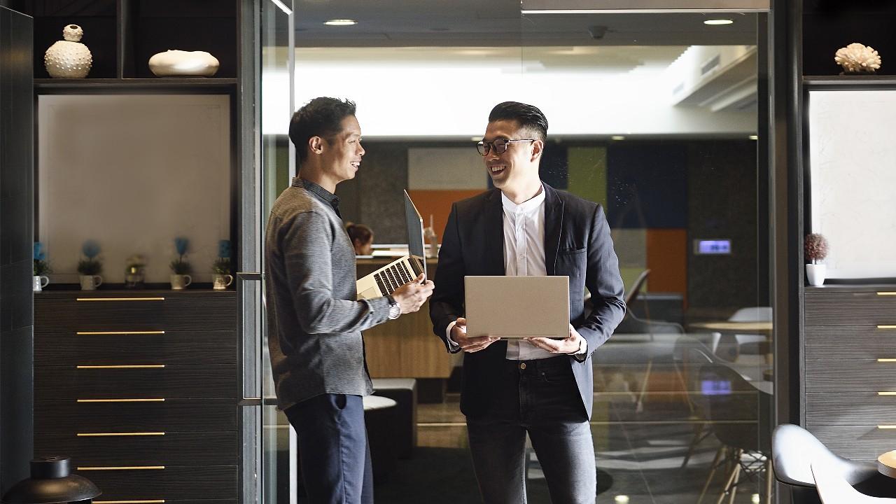 兩位男士拿著筆記本電腦站在辦公室裏;圖片使用於滙豐卓越理財20周年頁面。