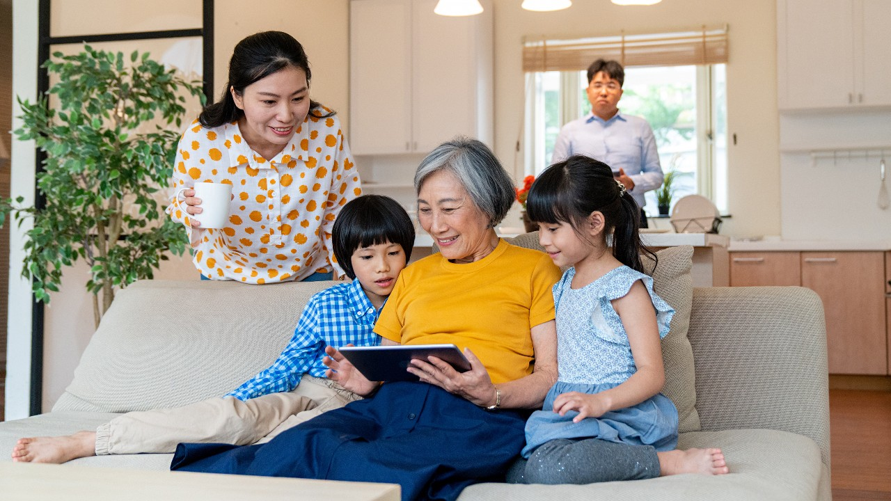 三代同堂一起開心地看著平板電腦;圖片使用於滙豐卓越理財20周年頁面。