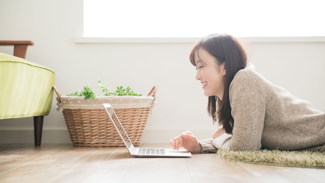 A lady is lying on the floor and using laptop; image used for HSBC Foreign Stock page.
