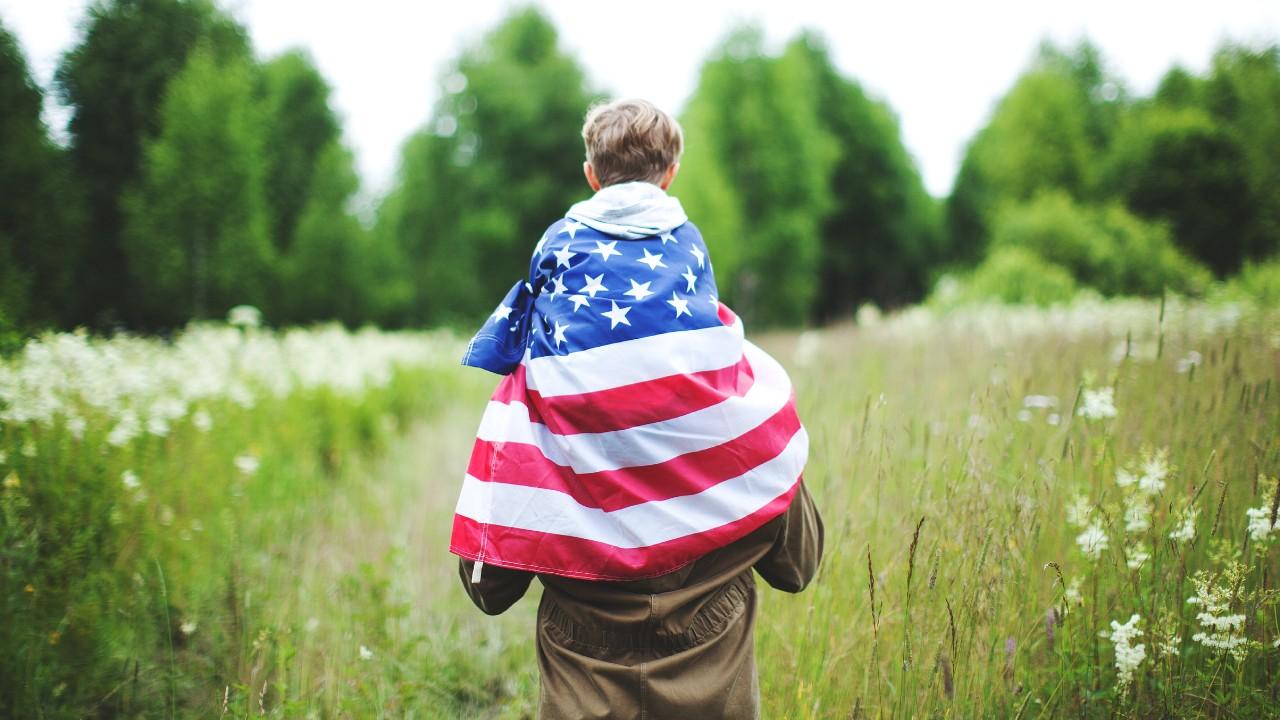 小孩包裹着美國國旗騎在父親肩膊上; 圖片使用於滙豐台灣優利定存優惠專案的頁面
