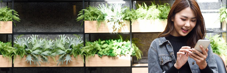 一位女士在辦公室綠植前瀏覽手機;圖片使用於數位理財抽大獎頁面
